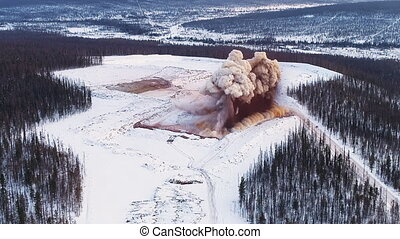 blow up of a mineral deposits. mined territory in field in forest in winter. coal mining. extractive industry for coal, top view aerial drone shot of explosion.