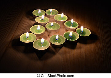 burning Candles in form of heart on a wooden background