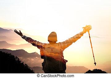 exposición doble, hombre, en, el, cima, de, montaña, mirar, salida del sol