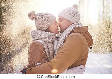 Expressing affection - Young dates in winterwear kissing in...