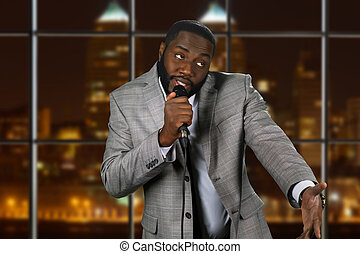 Expressive black man with microphone. Stand-up comedian on...