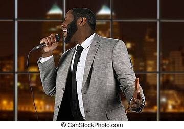 Expressive black singer with microphone.