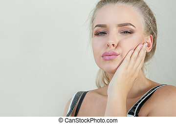 Expressive blonde model with perfect makeup posing on a grey background. Space for text