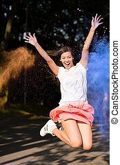 Expressive brunette asian woman jumping with Holi paint exploding around her