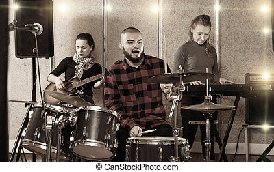 Expressive happy cheerful positive drummer with his bandmates practicing in rehearsal room