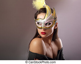 Expressive female model posing in carnival mask with red lipstick and looking vamp on empty copy space background. Closeup portrait