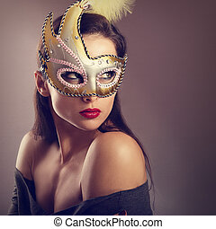 Expressive female model posing in carnival mask with red lipstick and looking vamp on empty copy space background. Closeup portrait. Toned art