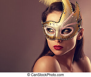 Expressive female model posing in carnival mask with red lipstick and looking vamp on empty copy space background. Closeup vintage portrait. Art