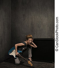 Expressive girl with guitar in a grungy room