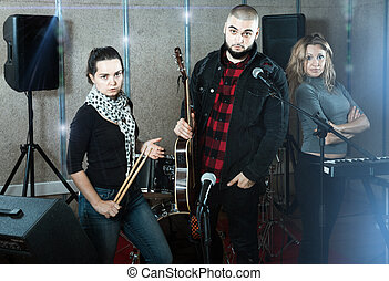 expressive group of rock musicians posing with instruments