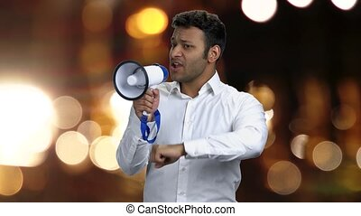 Expressive India man talking into megaphone. Young man is announcing a message with megaphone. Blurred bokeh lights on dark background.