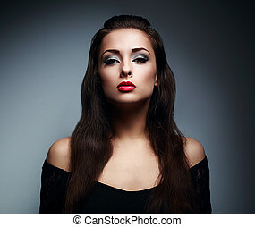 Expressive makeup female model with red lipstick and long hair posing on dark background