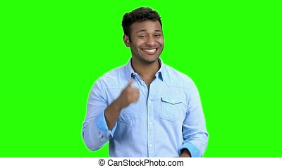 Expressive man is laughing on green screen. Cute Indian man...