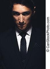 Expressive man portrait merging from the dark