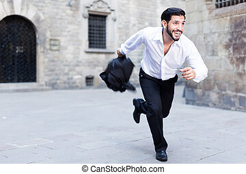 Expressive young man running past old city buildings