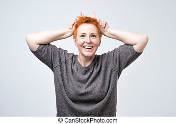 Expressive mature stylish woman with red hair winking flirty and holding fingers behind head like bunny ears