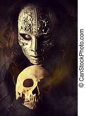 Mysterious man in iron mask holding skull. Steampunk. Fantasy. Halloween.