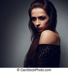 Expressive portrait of brunette makeup woman with mystical look in darkness