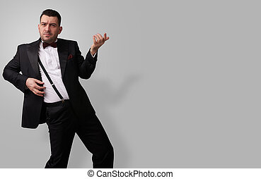 man in tuxedo playing rock-n-roll - Expressive young man in...