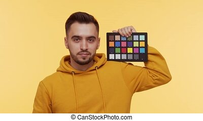 Expressive young man over vibrant background. Studio portrait of handsome person holding color checker. Coloristic and cinematography concept.