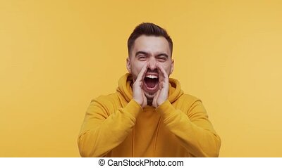 Expressive young man screaming and shouting over vibrant background. Studio portrait of handsome person.
