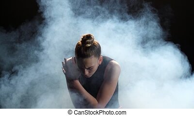 Expressive young woman dancing in clouds of smoke - Close-up...