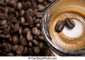 A cup of expresso macchiato with some roasted beans background.