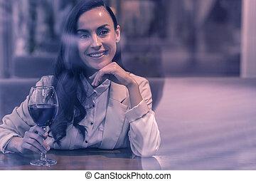 Positive joyful woman taking a glass of wine