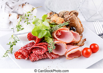 Exquisite meat plate, slicing different types of meat products.
