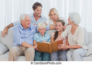 Extended cheerful family looking at a photo album in living...
