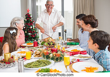Extended family at dining table for christmas dinner in house