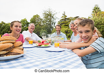 Extended family having dinner outdoors at picnic table...