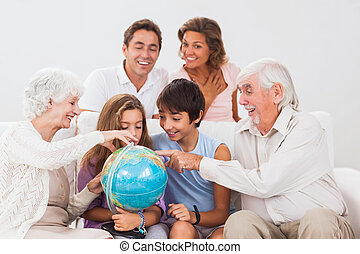 Extended family looking at globe