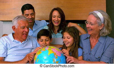 Extended family looking at globe to