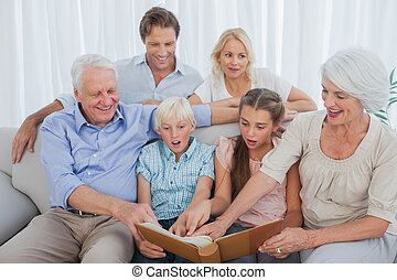 Extended family looking at their album photo in the living...