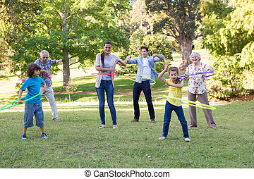 Extended family playing with hula hoops