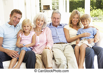 Extended Family Relaxing Together On Sofa