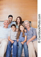 Extended family sitting on sofa in the living room