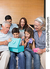 Extended family sitting on sofa wit