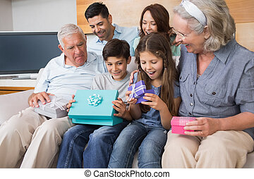 Extended family sitting on sofa with gift boxes in living room