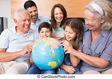 Extended family sitting on sofa with globe in the living...