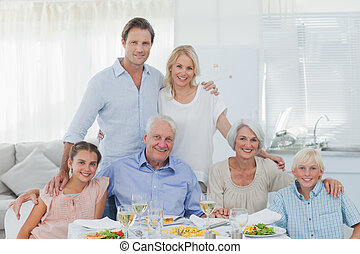 Extended family smiling at the dinner table in dining room