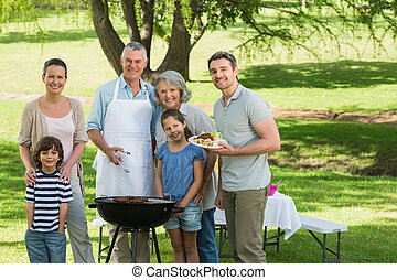 Extended family standing at barbecue in park