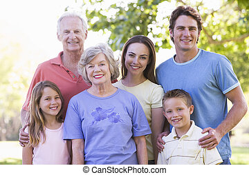 Extended family standing in park smiling