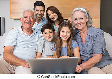 Extended family using laptop on sofa in living room - Happy...