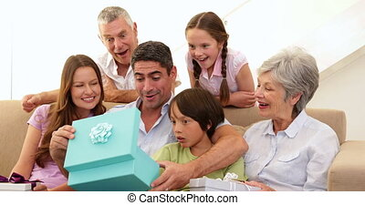 Extended family watching father open present