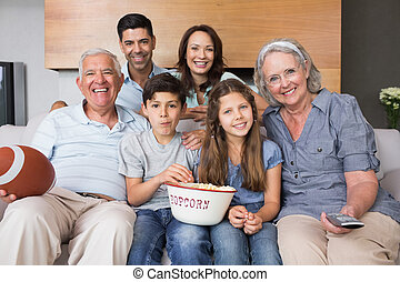 Extended family watching tv on sofa