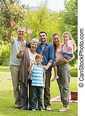 Extended family waving hands in par - Portrait of an...