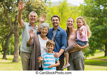 Extended family waving hands in park