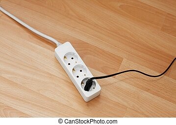 Plugged in electric extension cable on the floor